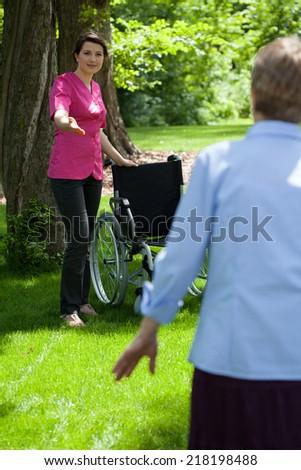 Nurse with elderly woman in garden of retirement home, vertical - stock photo