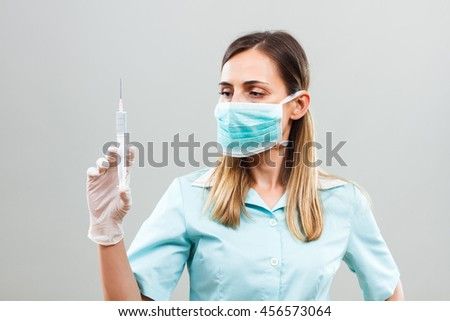 Nurse with protective mask holding injection.Nurse with injection - stock photo
