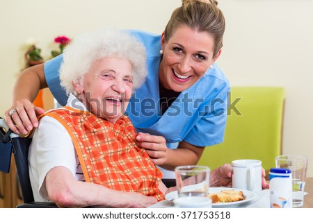 Nurse with senior woman helping with meal