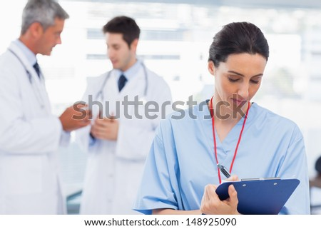 Nurse writing on a clipboard while doctors are talking together in medical office - stock photo