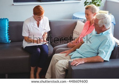 Nurse writing on clipboard in a retirement home - stock photo
