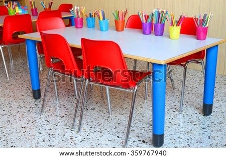 Nursery Classroom With Desks And Small Red Chairs