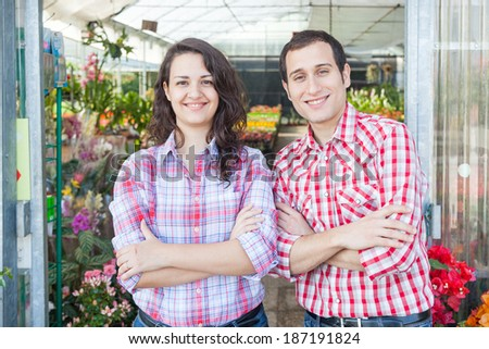 Nursery Owners with Greenhouse on Background - stock photo