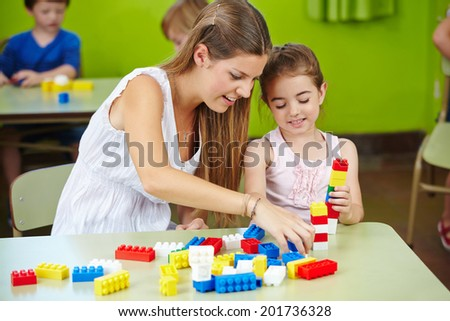 Nursery teacher and girl playing with building bricks in a kindergarten - stock photo