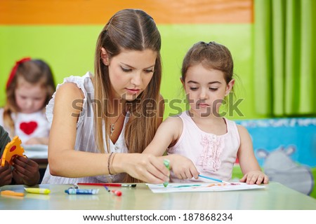 Nursery teacher helping girl painting with watercolor in a kindergarten - stock photo