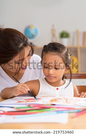 Nursery teacher helping little girl painting with watercolors - stock photo