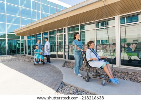 Nurses and male doctor with patients on wheelchairs at hospital courtyard - stock photo
