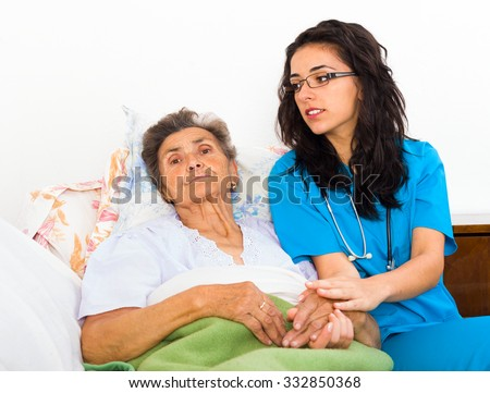 Nurses caring for elderly patients suffering from disease in nursing home.