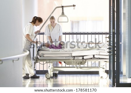 Nurses with patient in hospital bed - stock photo