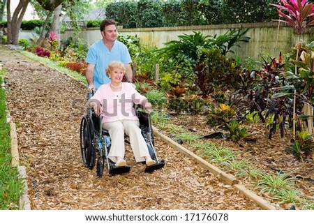 Nursing home orderly pushing a disabled senior woman through the garden. - stock photo