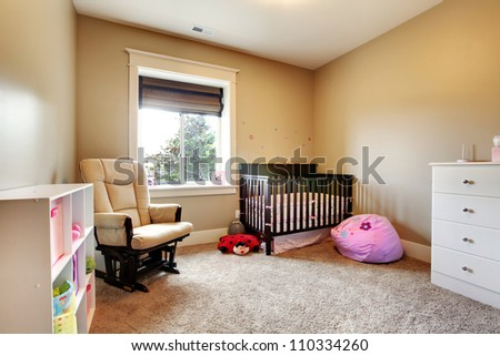 Nursing room for baby girl with brown wood crib and beige walls.
