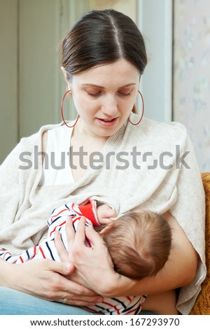Nursing three-month baby over home interior background - stock photo