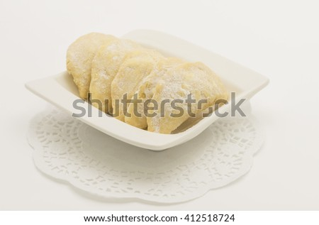 Nut cookies arranged in a white place with paper doilies at background.  Made of buttery, shortbread style dough with finely chopped nuts fillings. After baked, it is rolled in powdered sugar. - stock photo