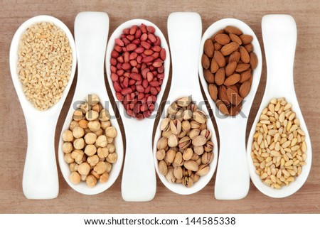 Nut selection in white porcelain scoops over papyrus background. - stock photo