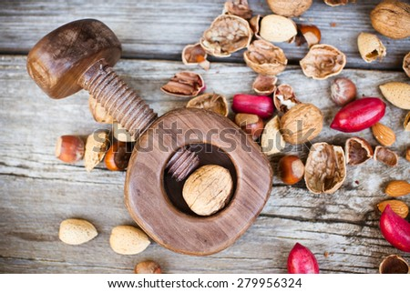 Nutcracker and nuts assortment  on wooden table. Above view. - stock photo
