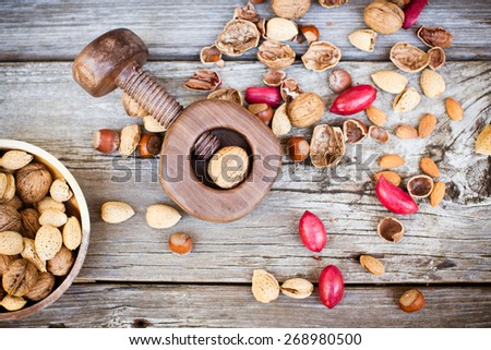 Nutcracker and nuts assortment  on wooden table. Also available  - stock photo