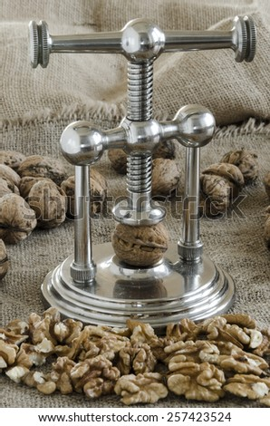 nutcracker and pile of walnuts in shell in soft diffused light - stock photo
