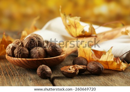 Nutmeg in wooden spoon on table on bright background - stock photo
