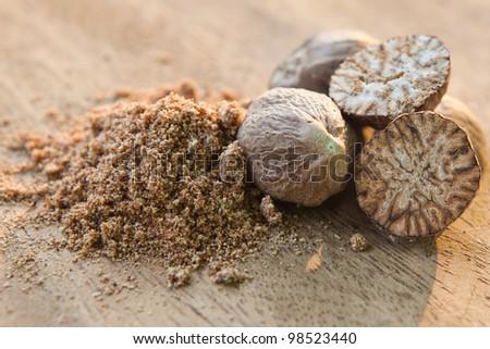 Nutmeg on wooden cutting board (shallow DOF) - stock photo