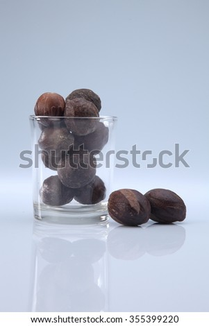 nutmeg seeds in a glass container - stock photo
