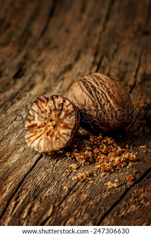 Nutmeg spice close up (macro) on vintage wood background. Layout with free text space. - stock photo