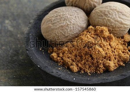 nutmeg whole and grated in a wooden bowl - stock photo