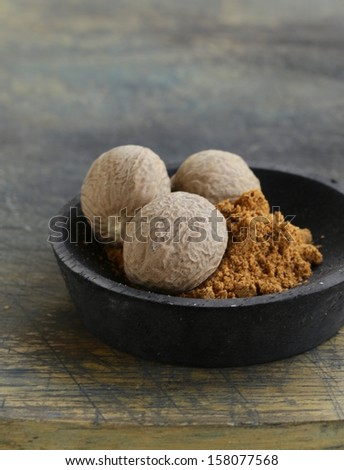 nutmeg whole and grated on a wooden table - stock photo