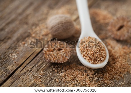 Nutmeg whole and grated on wooden background, selective focus - stock photo