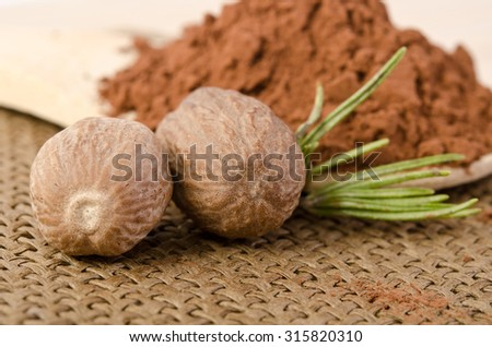 nutmeg with a sprig of rosemary and cacao powder in the wooden spoon on sacking background - stock photo