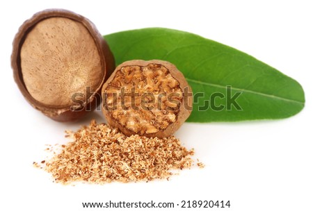 Nutmeg with green leaves over white background - stock photo