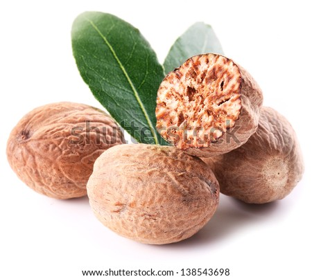 Nutmeg with leaves on a white background. - stock photo