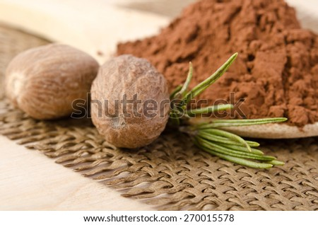 nutmegs with a sprig of rosemary and cacao powder in the wooden spoon on sacking base - stock photo