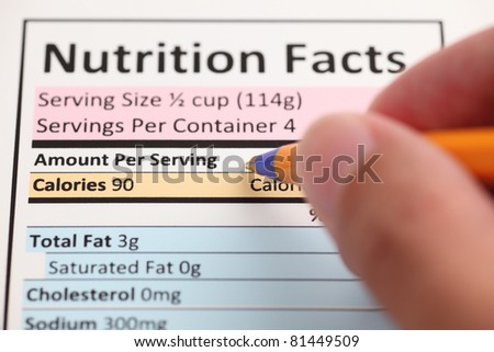 Nutrition Facts and hand with ballpoint pen. Close-up.