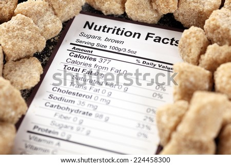 Nutrition facts of brown cane sugars with sugars background  - stock photo