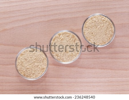 Nutritional yeast (deactivated yeast) in small recipients on a wooden plate - stock photo