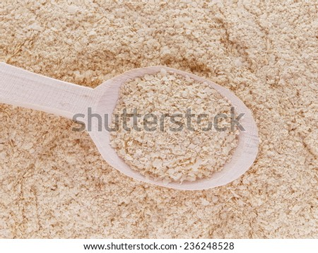 Nutritional yeast (deactivated yeast) in wooden spoon - stock photo