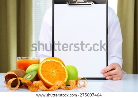 Nutritionist doctor with clipboard for diet plan in office - stock photo