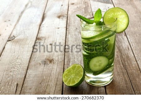 Nutritious detox water with lime and cucumber in a glass against a wood background - stock photo