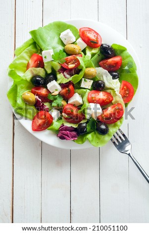 Nutritious fresh salad with feta, tomato, leafy greens and olives on a plate, overhead view on rustic white painted boards with copyspace - stock photo