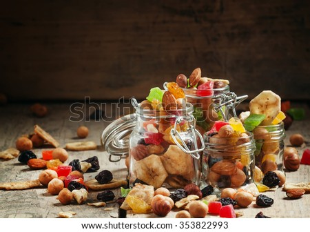 Nuts and dried fruits in glass jars on the old wooden table, selective focus