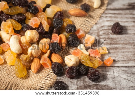 Nuts and dried fruits mix on a rustic sack and wooden background. Healthy food.