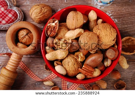 nuts assortment in red bowl and nutcracker on wooden table for christmas-top view  - stock photo