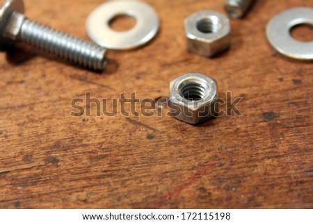 Nuts, bolts, and washers over wood background
