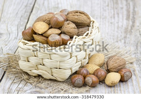 nuts in a basket on old wooden background - stock photo