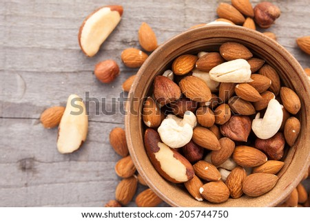 Nuts in bowl and around - stock photo