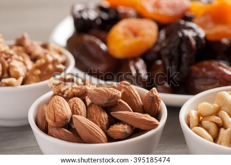 Nuts in ceramic bowls with dried fruits on a wooden table, selective focus, closeup shot - stock photo