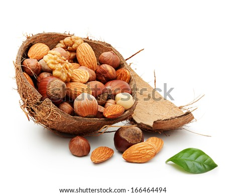 Nuts in cracked coconut isolated on white background. - stock photo