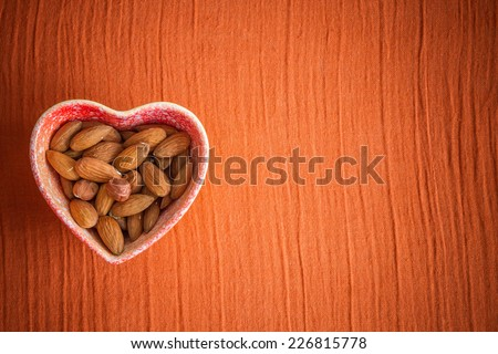 Nuts in dish in shape of heart with copy space on a textured background