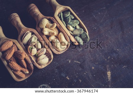 Nuts in the wooden scoops from above,selective focus and copy space - stock photo