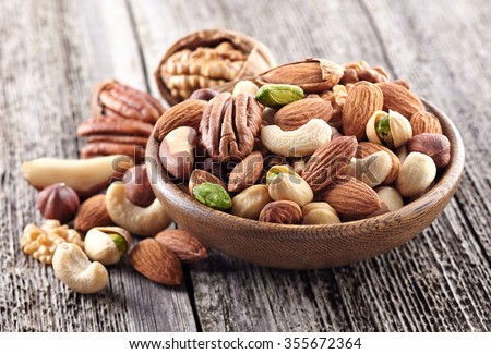 Nuts mix in a wooden plate - stock photo